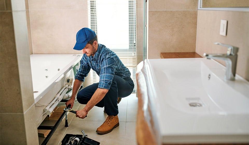 plumber replacing water pipes in bathroom renovation