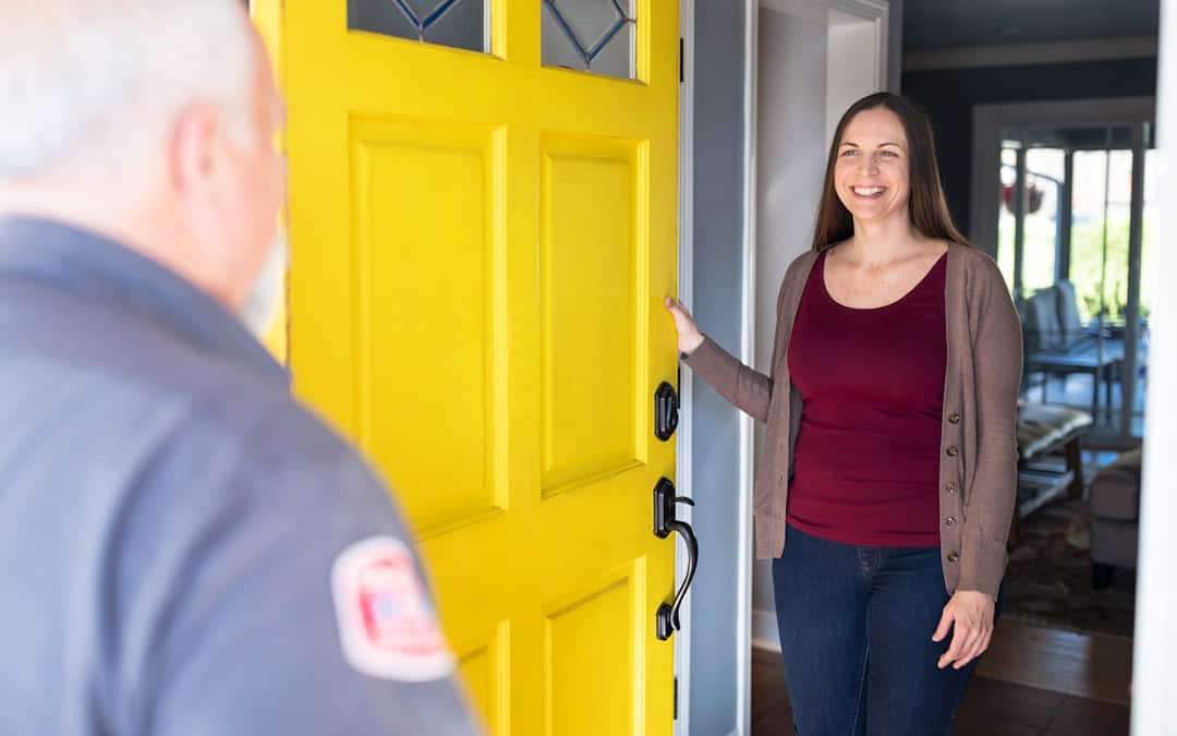 female homeowner greeting plumbing technician at the front door