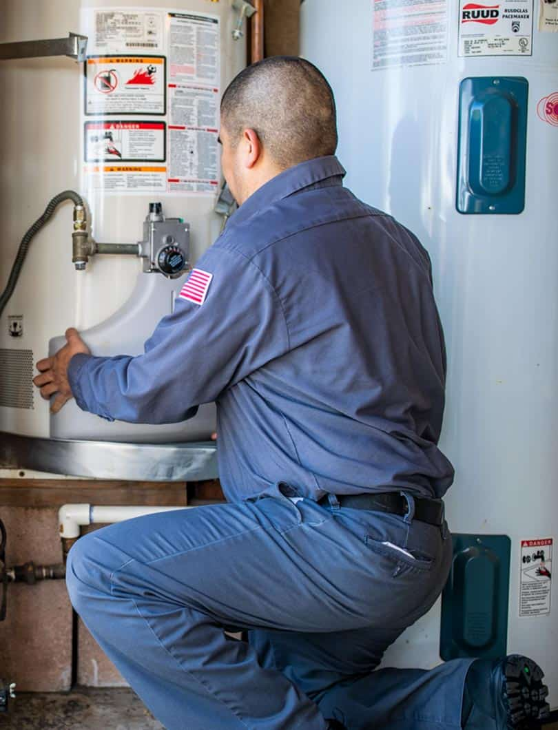 plumber checking the dial on home water boiler