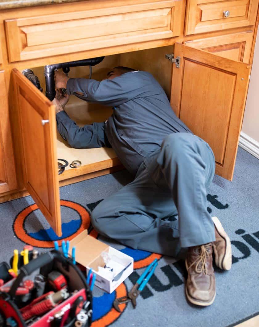 plumber repairing pipes below kitchen sink cabinets
