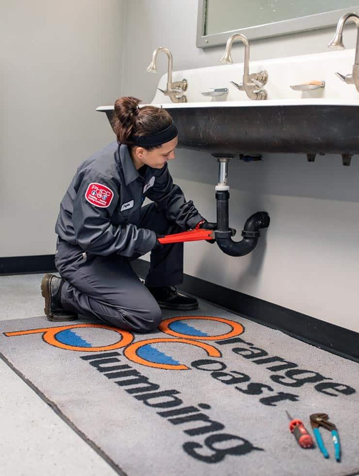 plumber tightening pipes underneath restroom sink