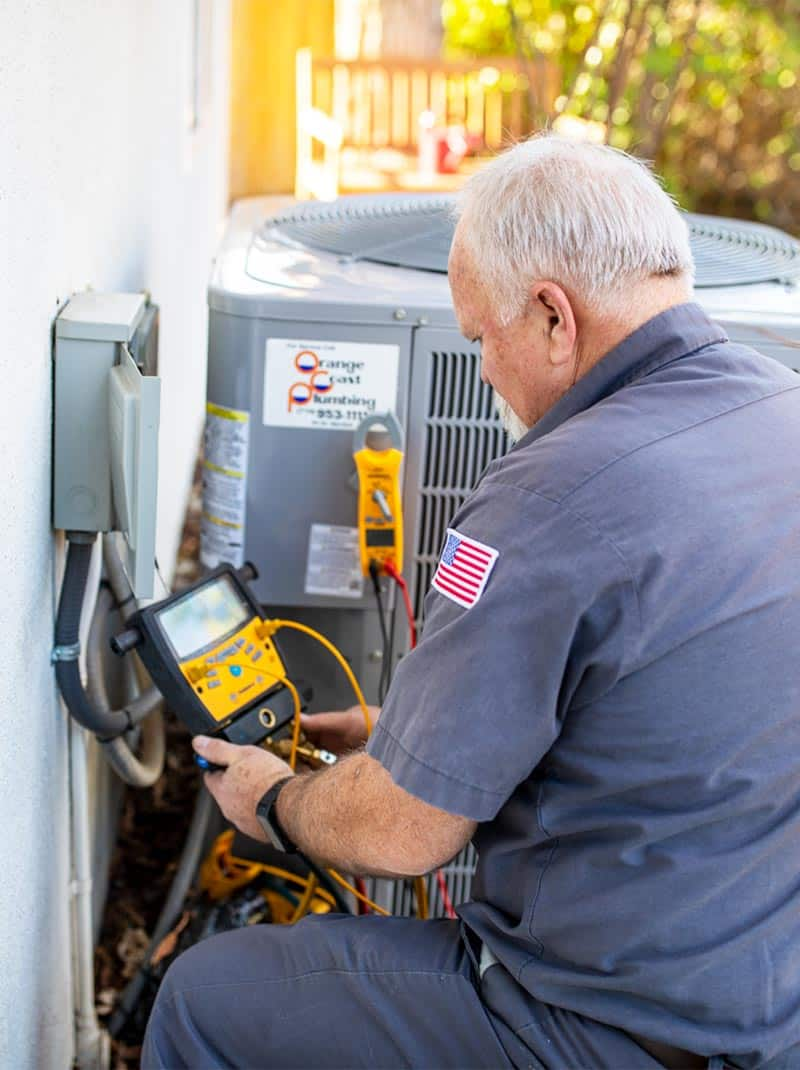 service technician inspecting home heating and air conditioning system