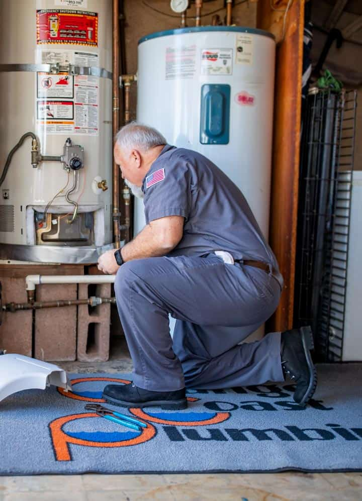 plumber checking cable lines on conventional hot water boiler