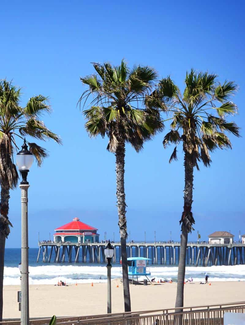 huntington beach pier on beach front with palm trees