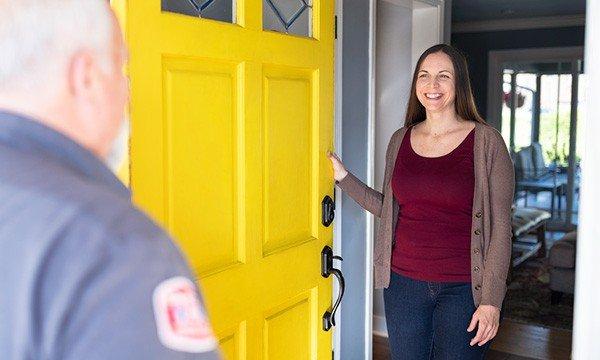 female homeowner greeting plumbing technician at the front door