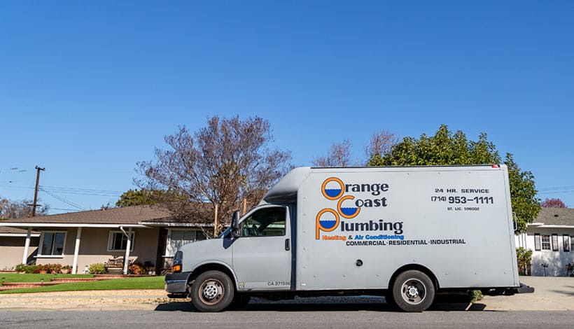 orange coast plumbing service truck parked in front of residential home
