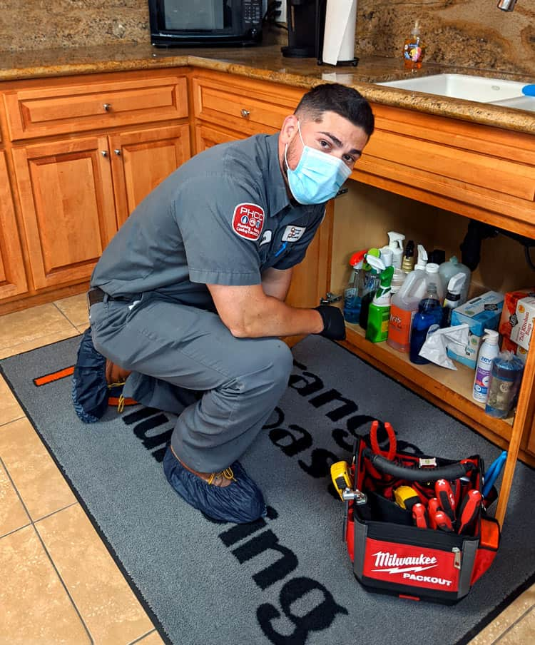 plumber with protective mask and gloves inspecting kitchen sink